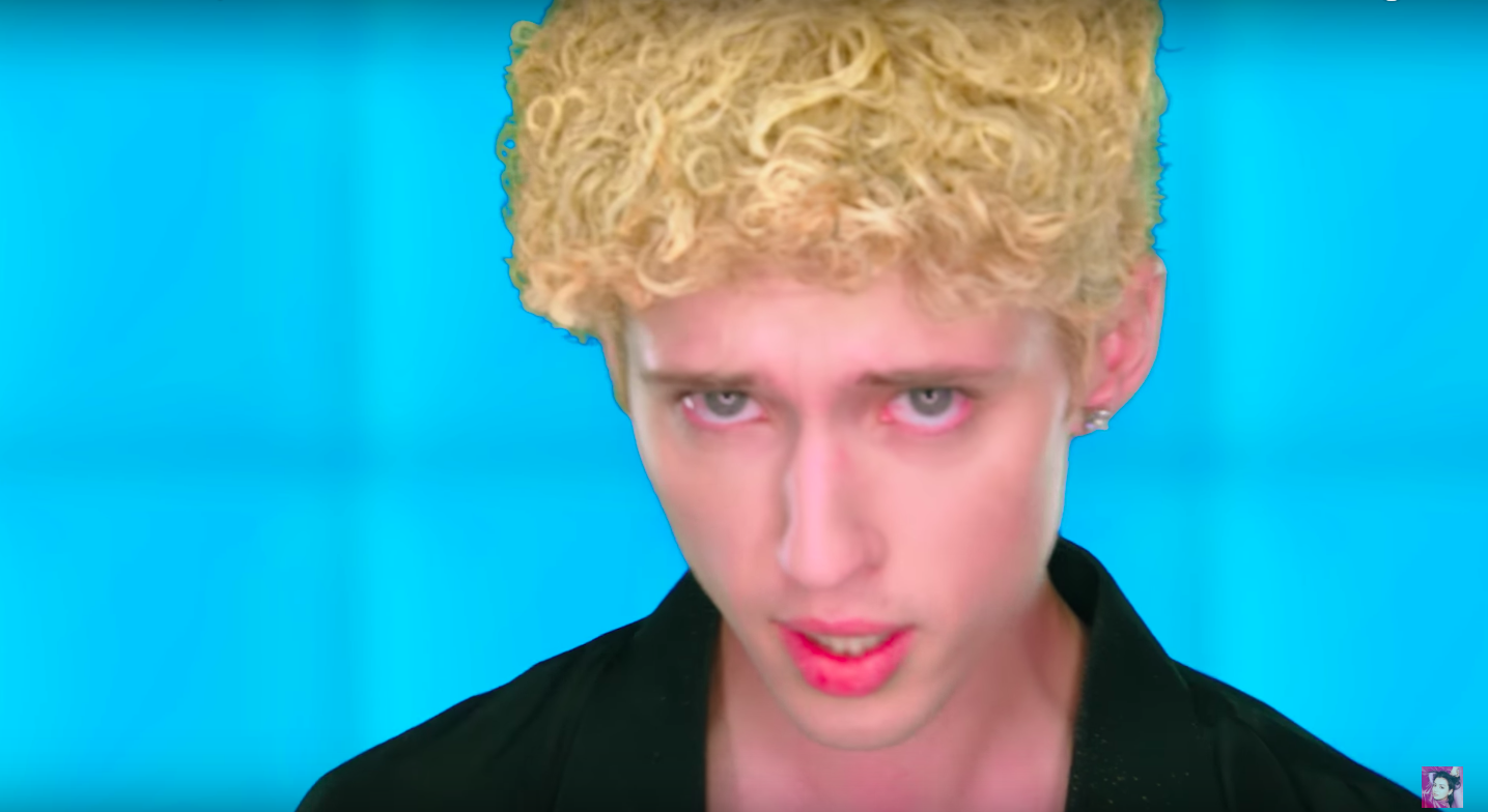 Troye Sivan looks at the camera, wearing a curly blond wig.