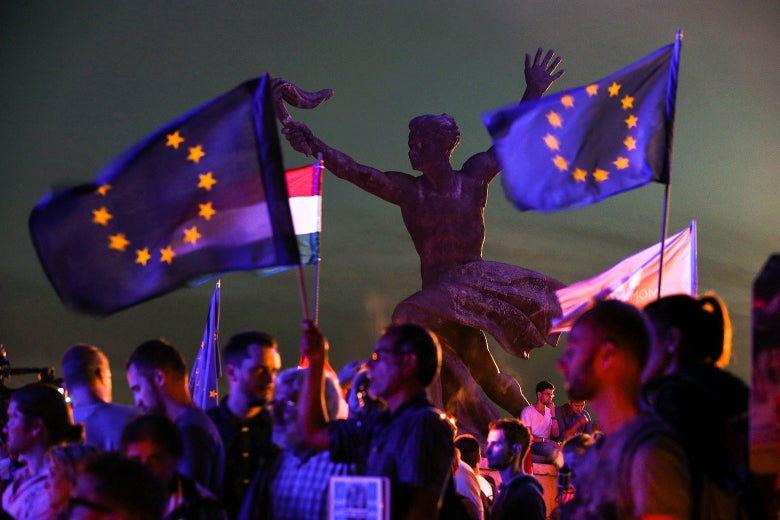 Protesters hold up EU flags.