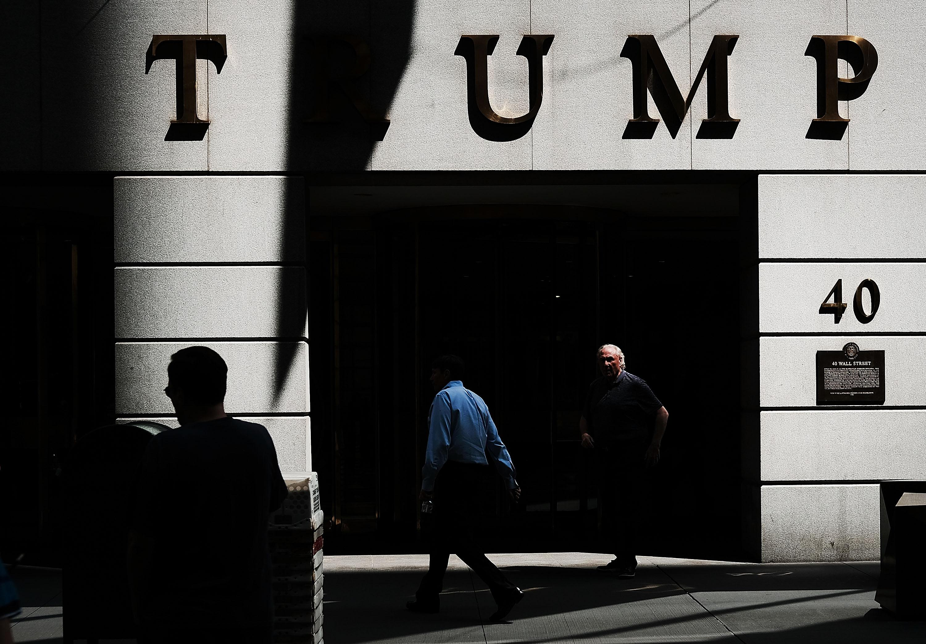 People walk outside of a building owned by President Donald Trump in Manhattan on August 24, 2018 in New York City.