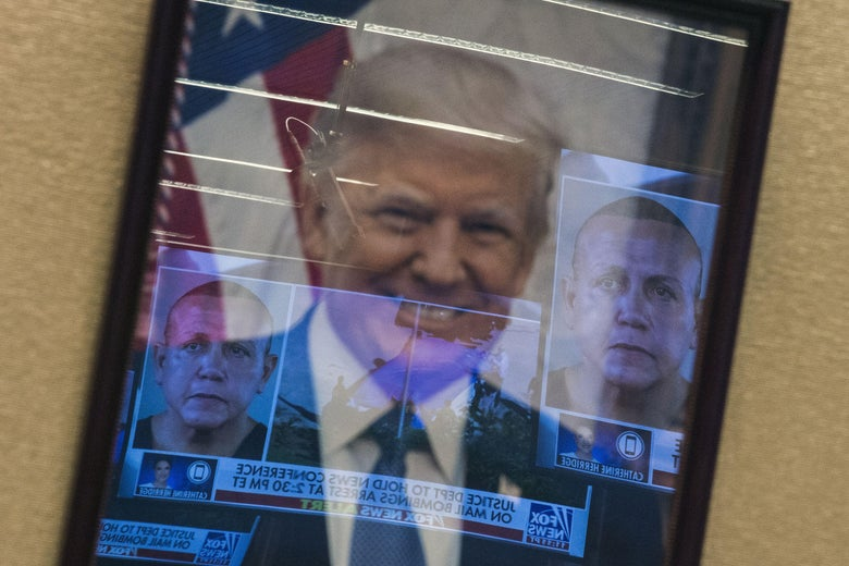 Mugshots of bombing suspect Cesar Sayoc are reflected on a portrait of U.S. President Donald Trump prior to a press conference at the Department of Justice in Washington, DC on October 26, 2018.