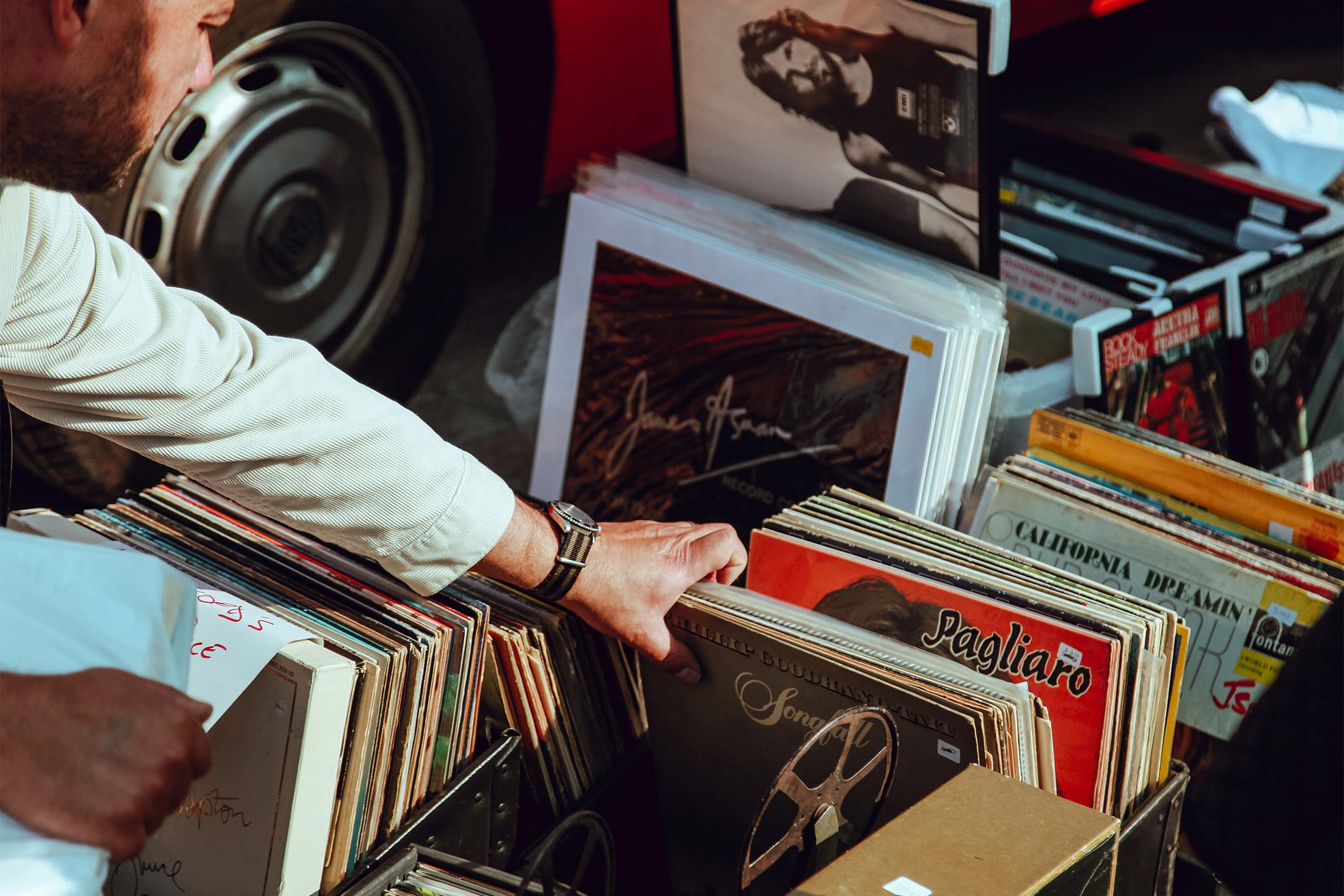 A man looking through a box of used records.