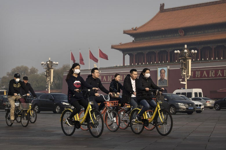 Chinese commuters ride bike share through Tiananmen Square on March 29, 2017 in Beijing, China.