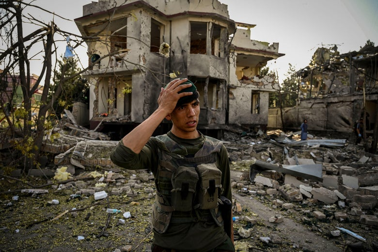 An Afghan man wearing U.S. military gear stands in front of rubble putting his right hand to his head in apparent dismay