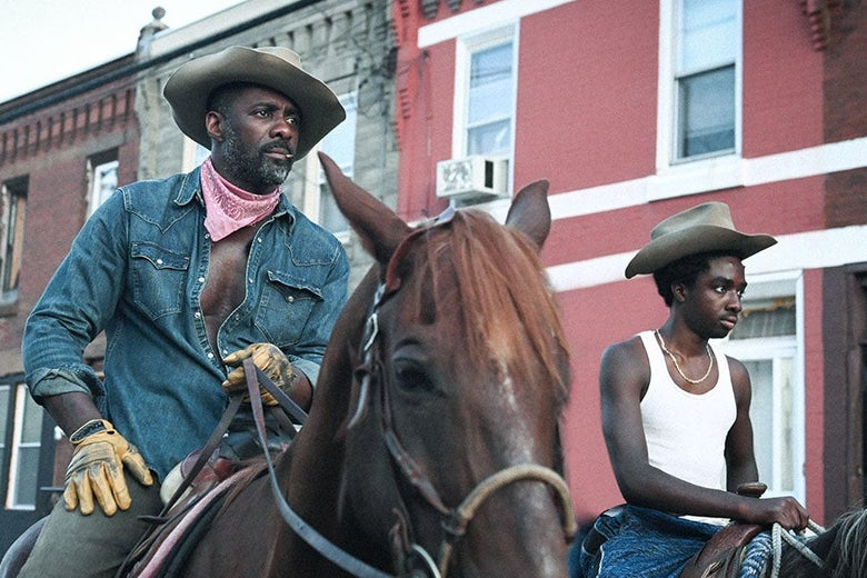 Two Black men ride horses through the streets of Philadelphia.
