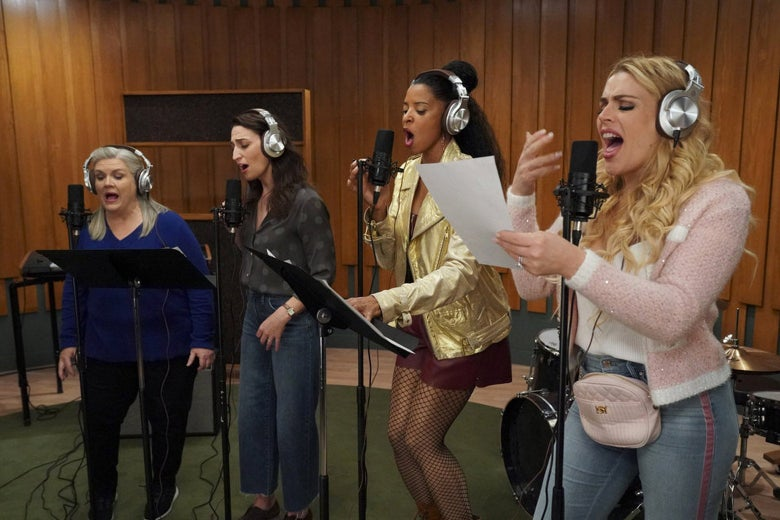 Four women with headphones on sing into microphones in a studio.