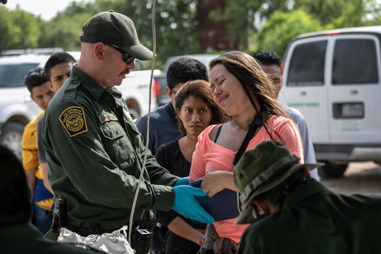 A woman who has recently arrived in the United States to seek political asylum appears distressed as a U.S. Border Patrol agent checks her arm while wearing blue medical gloves.