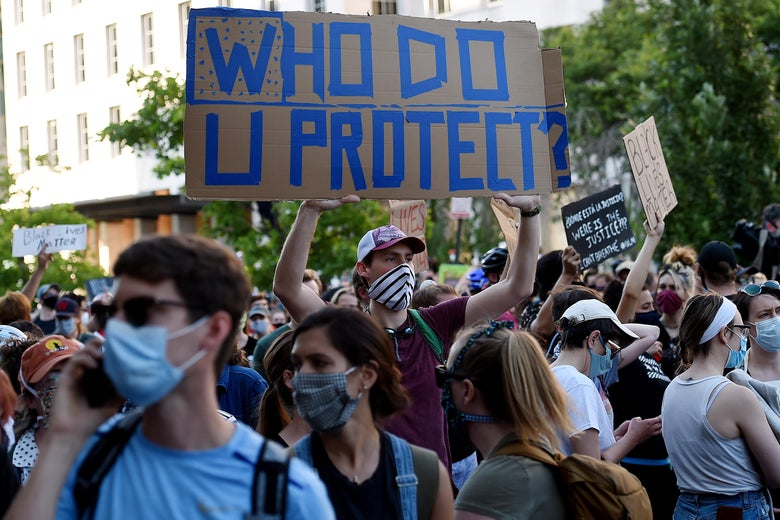 "Amid a group of protesters wearing masks, a man holds a sign that says ""Who Do U Protect?"""