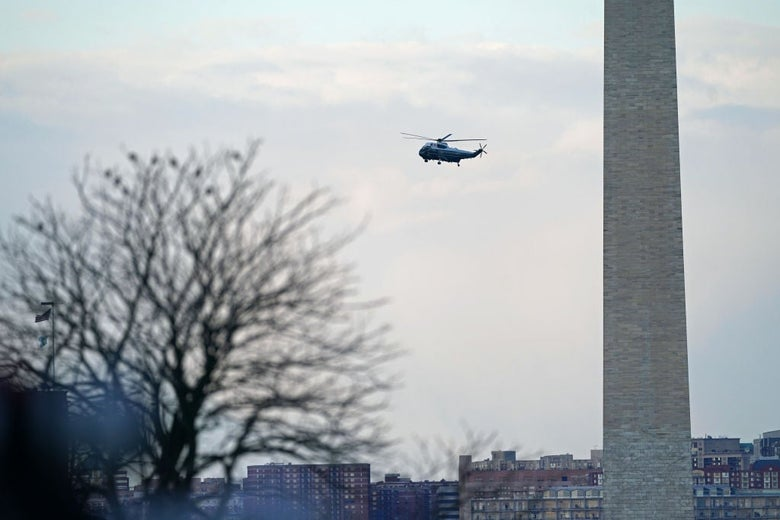 A helicopter seen in the distance flies past the Washington Monument.