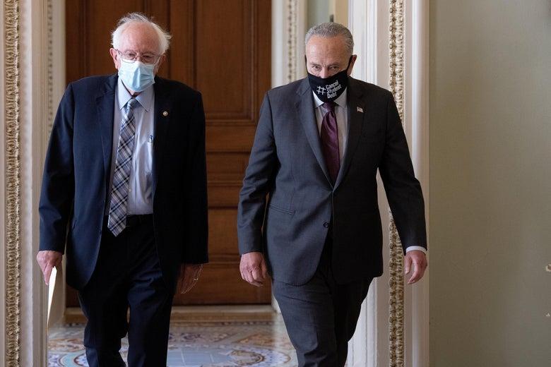 Bernie Sanders and Chuck Schumer walk side by side in a hallway, both wearing masks