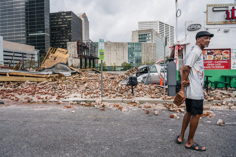 Big Chief Darryl Montana stands holding a brick in front of a pile of rubble left behind by Hurricane Ida