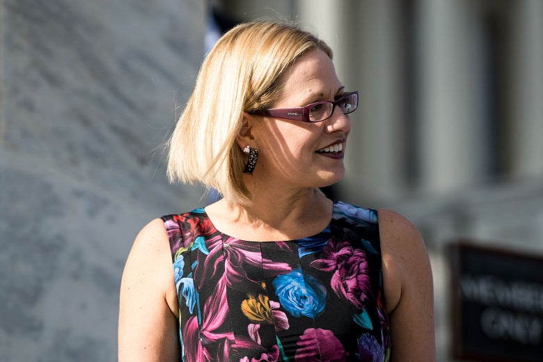 Kyrsten Sinema on the House steps wearing a multicolored floral sleeveless dress, a pair of chunky Chanel glasses, and glittery hoop earrings.