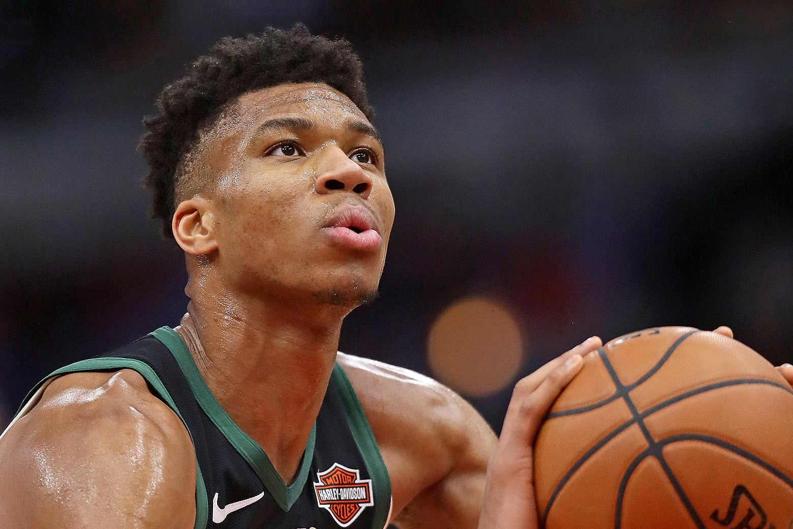 Giannis Antetokounmpo holding a basketball, preparing to shoot.