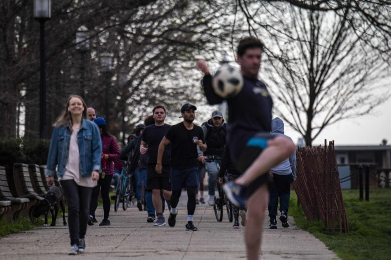 People walk and jog, and a man kicks a soccer ball, on a crowded path.