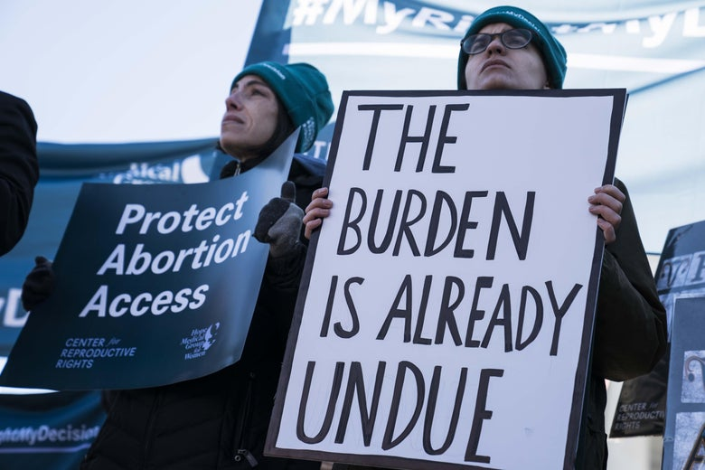 """A woman in a beanie holds a sign that says """"Protect Abortion Access."""" A person next to her holds a sign that says """"The Burden Is Already Undue."""""""