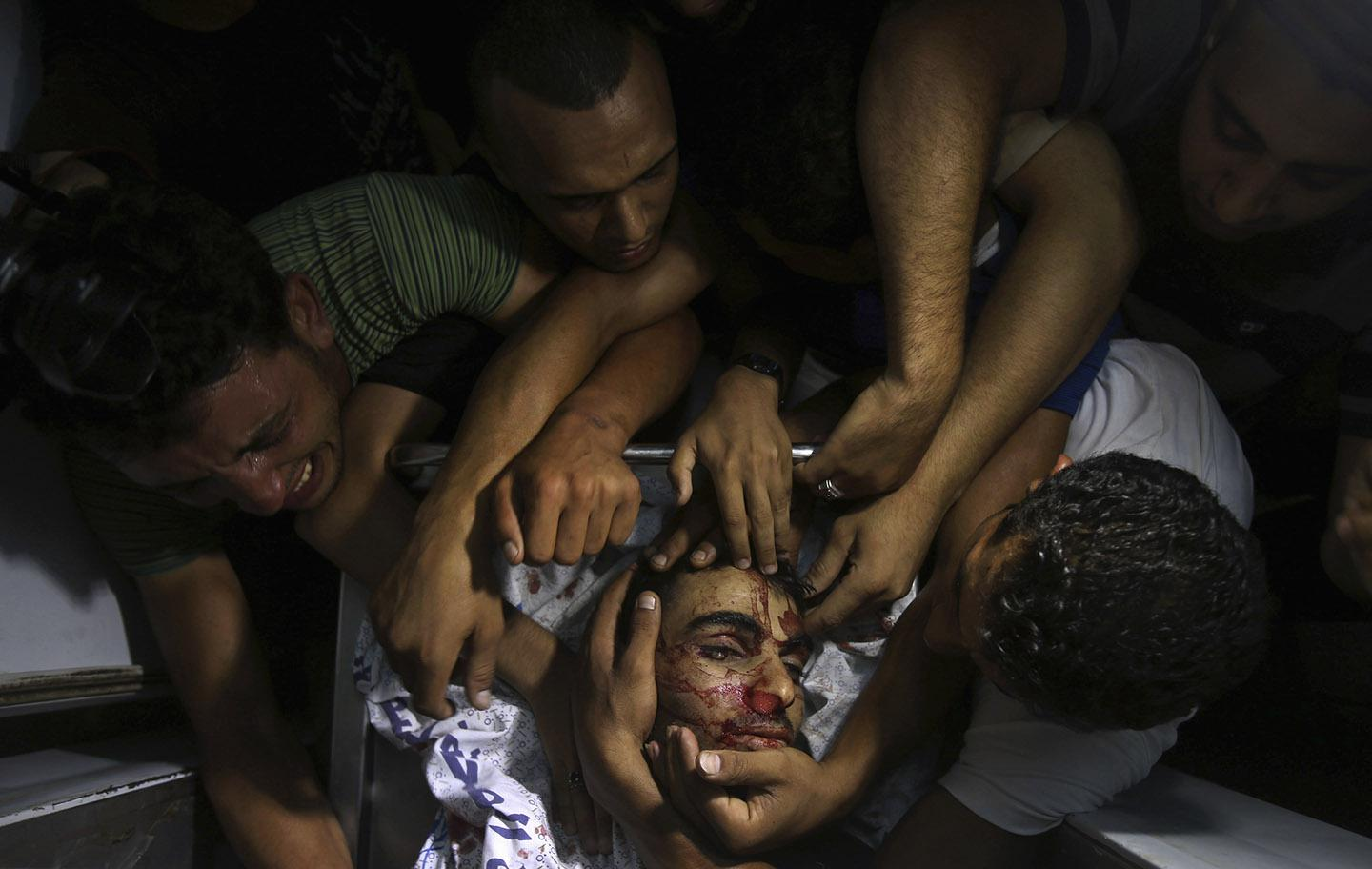 People mourn around the body of a Palestinian militant at a hospital morgue in the central Gaza Strip July 6, 2014.