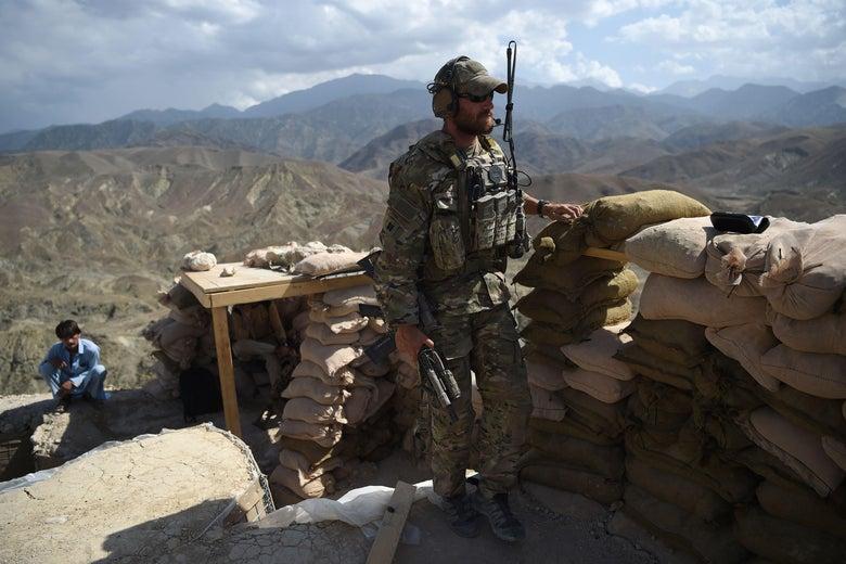 A soldier stands beside a sandbag barrier overlooking a hillside in Afghanistan.
