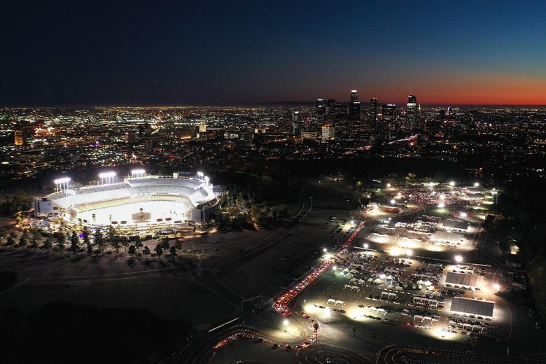 An aerial view of cars are lined up at the mass COVID-19 vaccination site at Dodger Stadium at night, with the downtown skyline in the background.