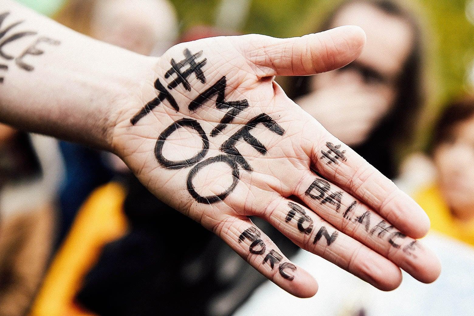 A protestor shows the messages #MeToo and #BalanceTonPorc.