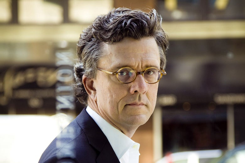 A middle-aged white man with small glasses and curly hair.