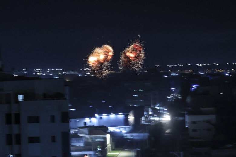 Two fiery explosions can be seen in the night sky on Gaza city skyline.