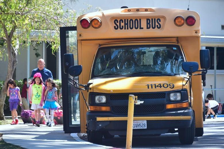 Children walk past a school bus.