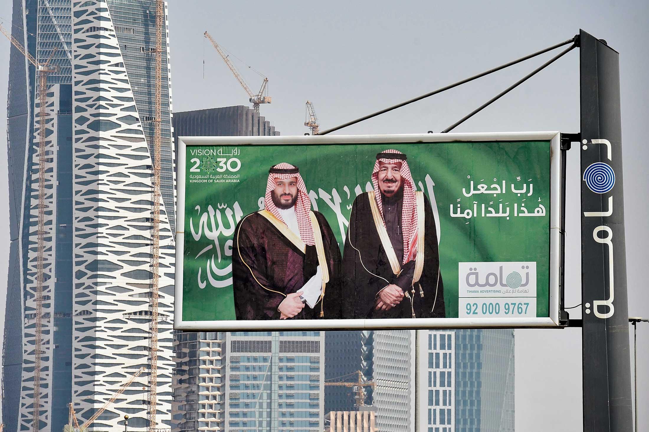 Portraits of Saudi Arabian King Salman and his son, Crown Prince Mohammed Bin Salman, on a printed sign