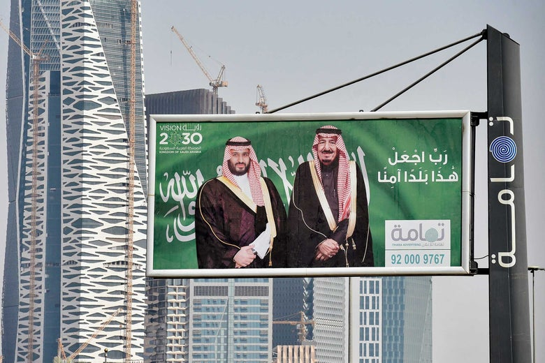 Portraits of Saudi Arabian King Salman and his son, Crown Prince Mohammed Bin Salman, on a printed sign