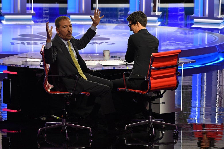 Chuck Todd turns around to face the audience, arms raised in frustration, next to Rachel Maddow. They're both sitting at a desk on the debate stage.