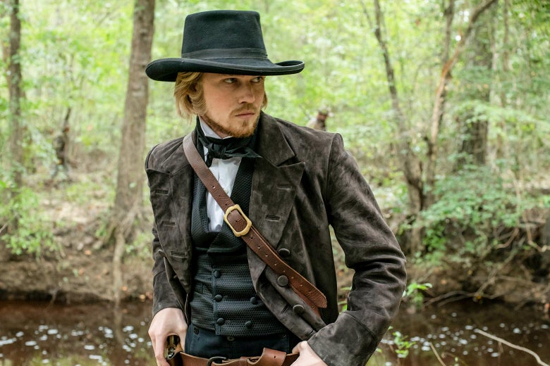 Joe Alwyn as Gideon, wearing 19th century garb and looking around in a forest.