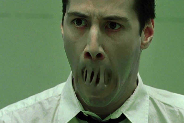 Keanu Reeves, in a still from the Matrix, staring in horror as his lips seal together.