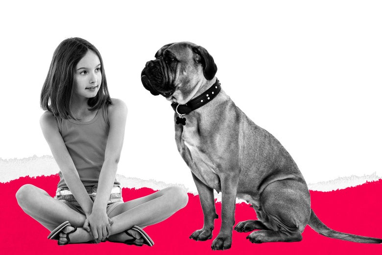 A girl sitting cross-legged next to a dog.