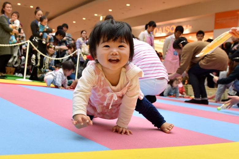 A baby crawling towards the camera, smiling.