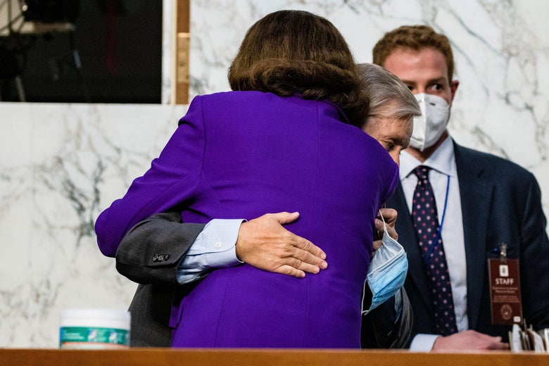 Dianne Feinstein hugs Lindsey Graham, who is holding is mask in his hand.