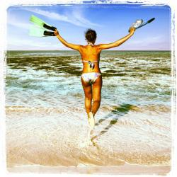 Joyful woman in bikini runs to the sea