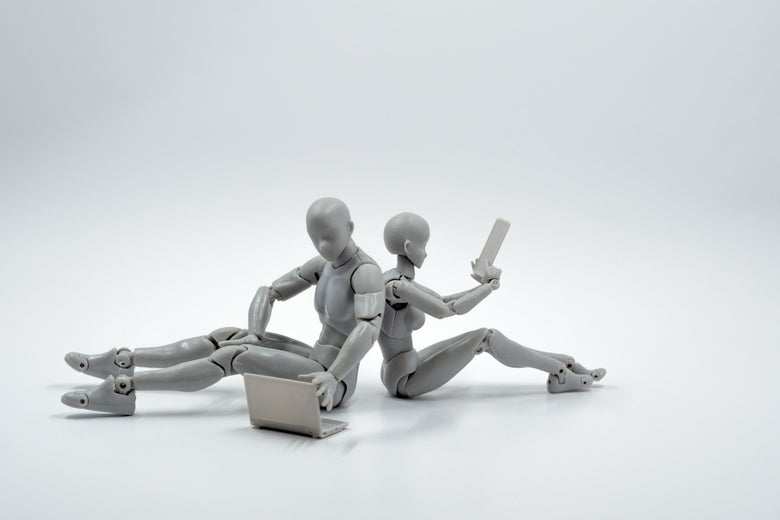 Two humanoid robots sit back to back while one looks at a laptop and the other at a tablet.