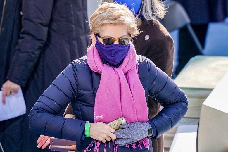 Elizabeth Warren wears sunglasses, a purple face mask, a pink scarf, and a purple puffer coat.