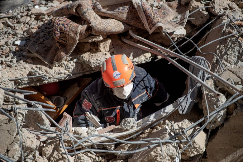 A rescue worker with a mask and hard hat is seen amid the rubble of a collapsed building.