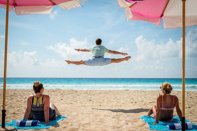 Edgar does a midair split on the beach as two women look on.