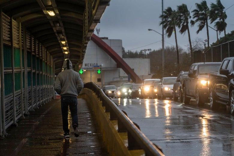 A man in a hoodie walks on a sidewalk as a line of cars pass him against a rainy, gray sky.