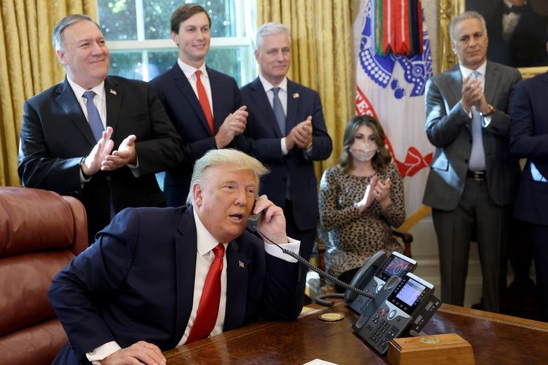 Donald Trump talks on a phone behind the Resolute Desk while staffers, including Mike Pompeo and Jared Kushner, applaud.