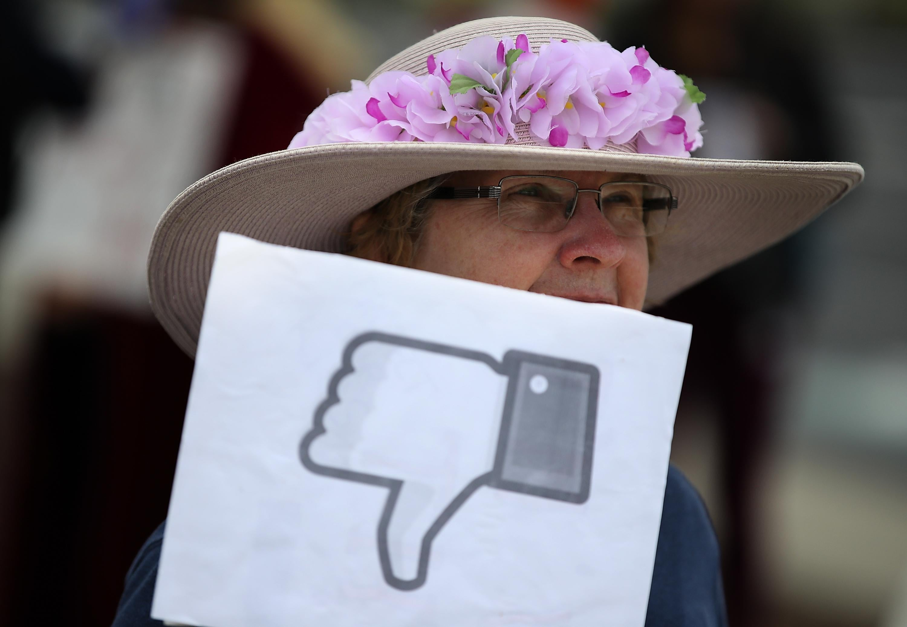 Woman holds a sign with the Facebook thumbs down symbol
