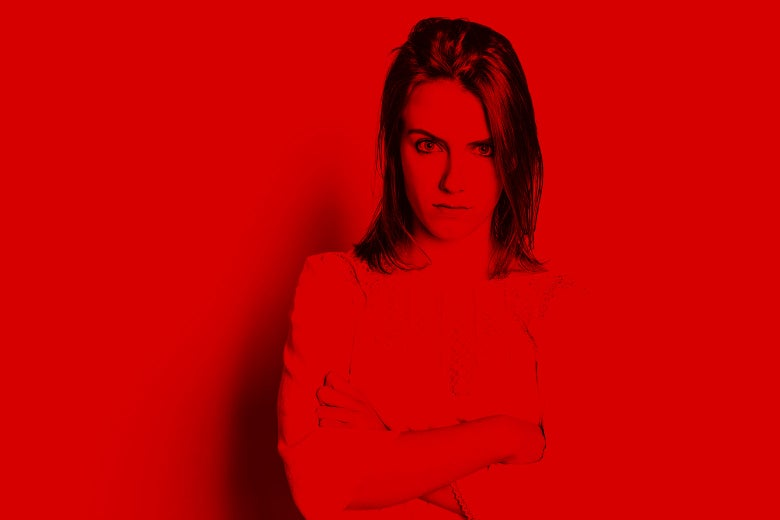 Lit in red, a young woman stands looking angry with her arms crossed.