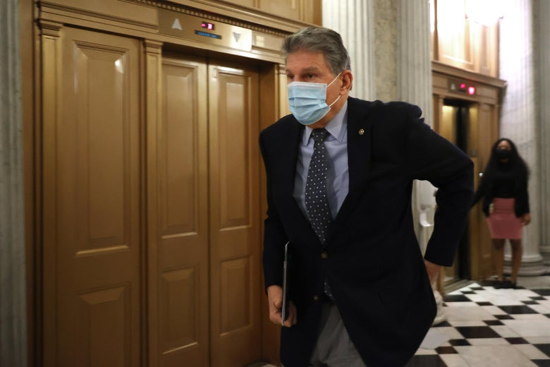 Joe Manchin wears a suit and tie and a face mask while carrying a folder and walking down a hallway.