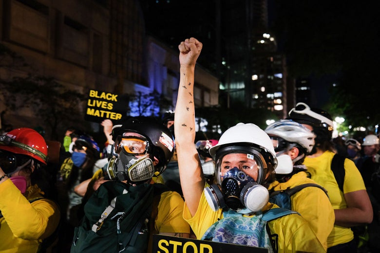 A protester wearing a mask and helmet holds up a fist amid a crowd of others.