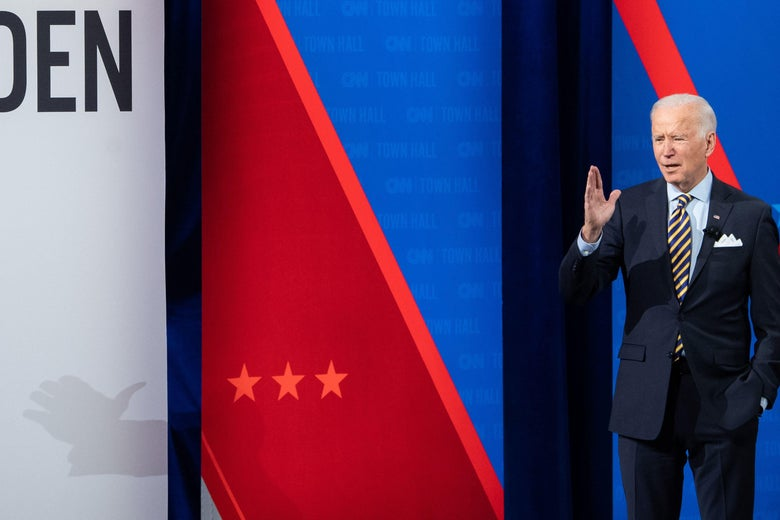 Joe Biden stands up and gestures onstage with one hand in his pocket at a CNN town hall.