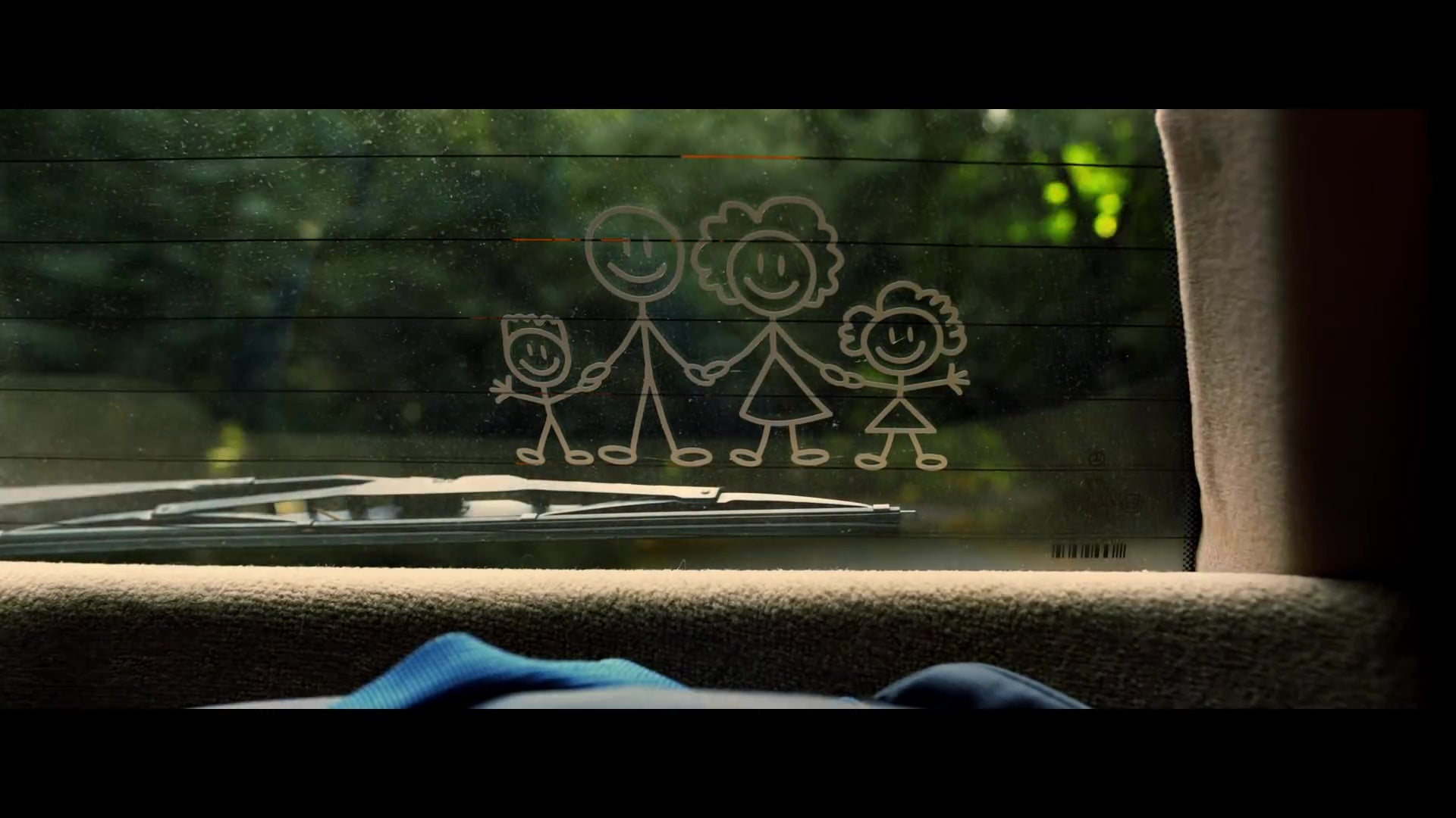 A still from Us depicting a car rear-window decal of a stick-figure family of four people,