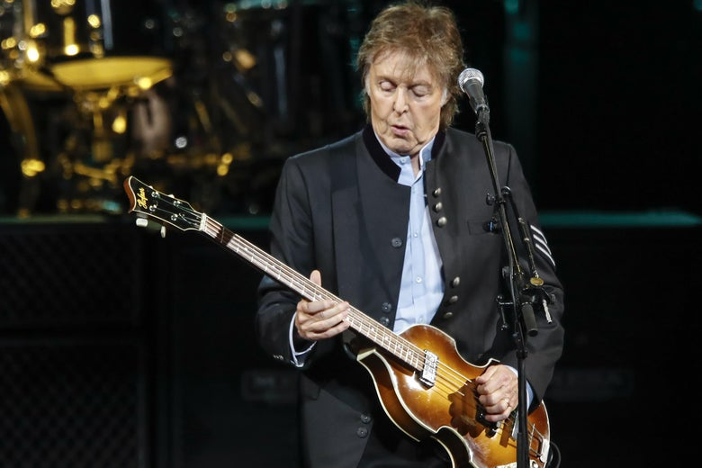 Paul McCartney plays a guitar onstage.