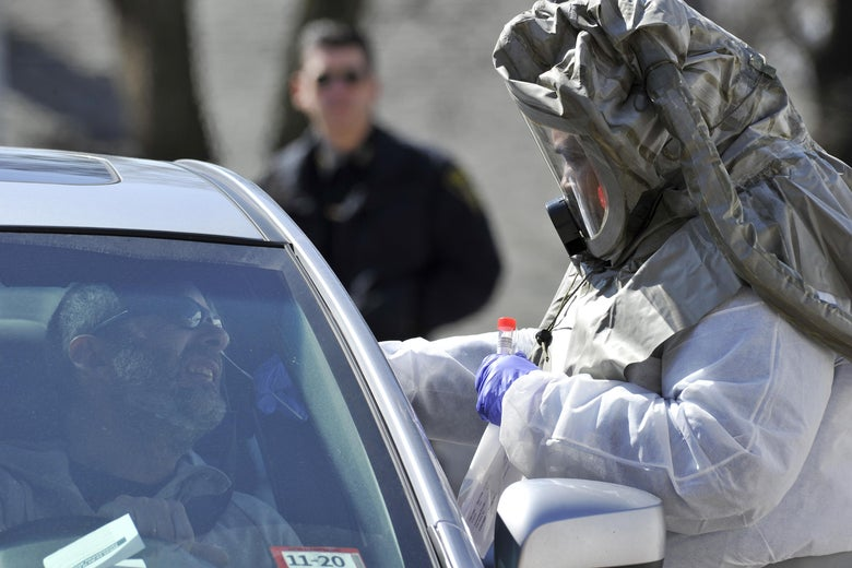 A man sits in his car with his face angled up as a person in protective gear takes a swab of his nose.