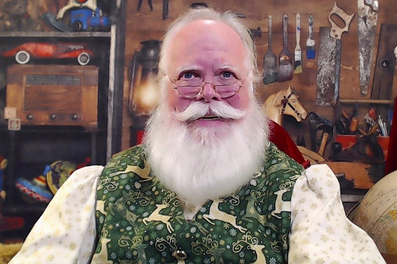 Stephen Arnold smiles as Santa Claus, wearing a green vest with a reindeer pattern over a white shirt with a snowflake pattern. He sits in Santa's workshop with toymaking tools hanging in the background.