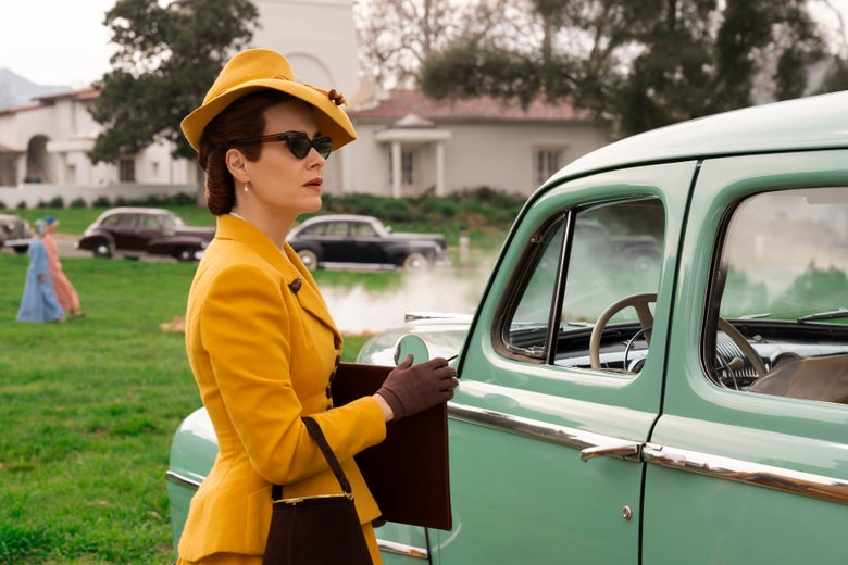 Sarah Paulson as Mildred Ratched, in a yellow suit with sunglasses in front of an old-fashioned automobile.